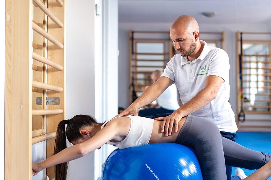 Девојка Вежба на Пилатес Лопти у Сали Зоне Комфора са Терапеутом на Третману Програм по Шроту