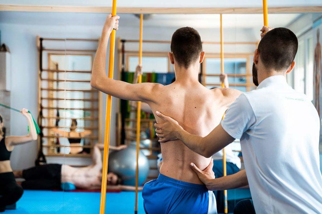 Терапеут и Клијент са Шипкама Вежбају у Сали Зоне Комфора на Третману Програм по Шроту